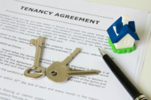 Tenancy agreement key and pen with symbolic miniature house